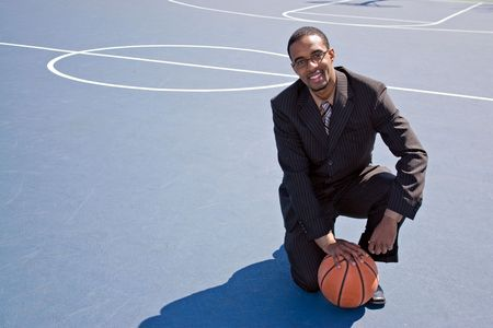 A young African American man in a business suit posing on the basketball court with a ball.  Works great for coaching or recruitment concepts. photo