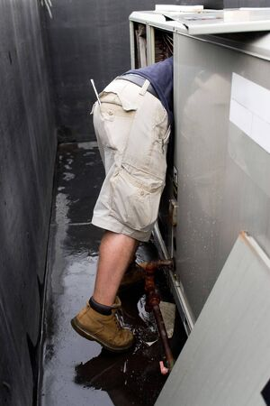 condicionador: An HVAC technician repairing a commercial unit. Banco de Imagens