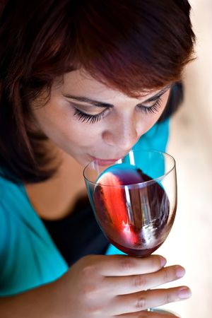 A woman sipping on her glass of red wine.  Shallow depth of field with focus on the eyelashes. Stock Photo - 6579176