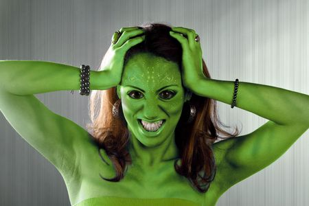 sci fi: A green alien or Martian woman posing over a silver brushed metal backdrop.