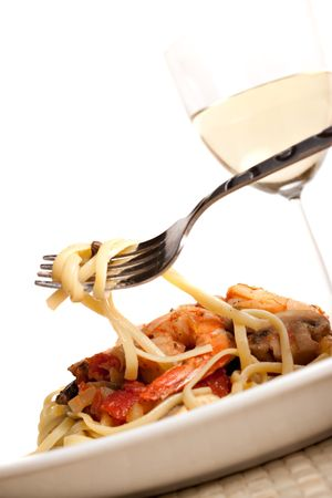 A delicious shrimp and pasta dish along with a glass of pinot grigio white wine.  Shallow depth of field.