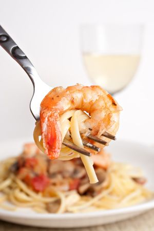 A delicious shrimp scampi pasta dish along with a glass of pinot grigio white wine.  Shallow depth of field with focus on the fork and shrimp. Archivio Fotografico