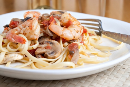 A delicious shrimp scampi pasta dish with mushrooms and diced tomatoes along with a glass of pinot grigio white wine.