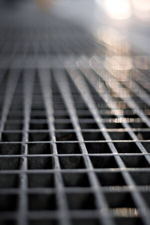 Closeup of a sidewalk subway grate with shallow depth of field. photo