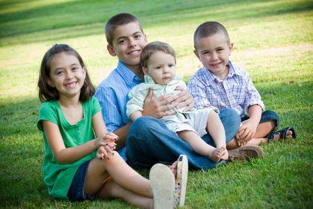 一人の女の子と 3 人の男の子と 4 人の子供のグループ。兄弟および姉妹の素敵な取得します。男の子の鋭い焦点とフィールドの浅い深さ。 写真素材
