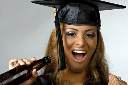 A young woman celebrating her graduation with a bottle of beer. photo