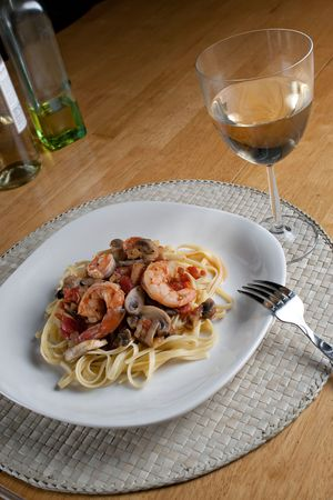 A delicious shrimp with linguine pasta dish and a nice glass of pinot grigio white wine.  photo