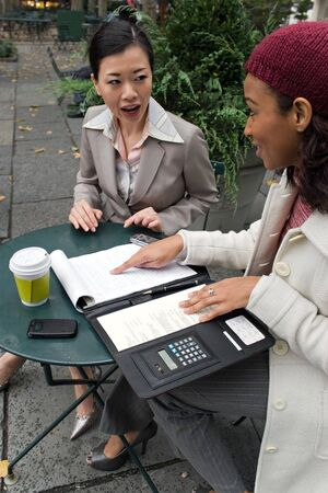 Two young business women discussing a group or team project in the park. photo