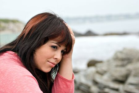 A young plus size model looking depressed or thinking deeply about something by the sea shore. Stock Photo