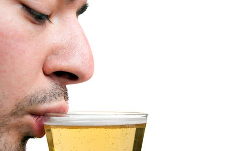 A young man sipping a tall glass of beer isolated over white.  Shallow depth of field with sharp focus on the lip and beer. photo
