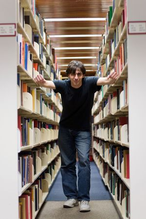 aisles: A young man standing in the aisles of the library book shelves.