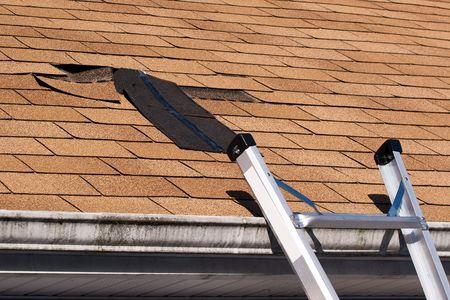 toiture maison: Fixation des bardeaux de toiture endommag�e.  Une section a �t� arrach�e apr�s une temp�te avec des vents provoquant une fuite potentielle. Banque d'images