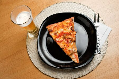 A single slice of buffalo chicken pizza and a glass of light beer.   photo