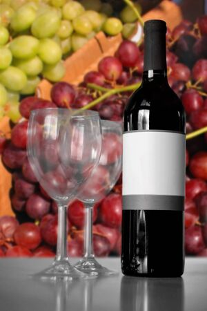 A still life shot of a single wine bottle and a pair of empty glasses with selective color in front of some grapes.  Shallow depth of field. photo