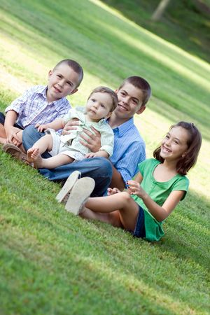 behaving: A group of four kids with one girl and three boys.  All siblings are getting along nicely. Stock Photo