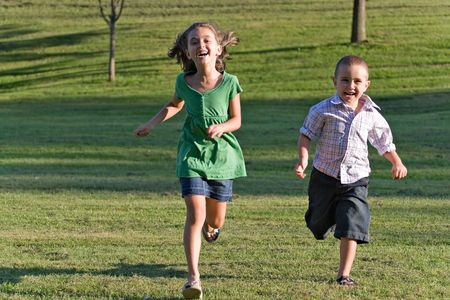 children playing outside: Two happy little kids having fun while running through the grassy field and racing against each other.