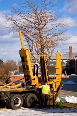 huge tree: A piece of heavy duty machinery that  transplants trees with its large scooping claw in action. Stock Photo