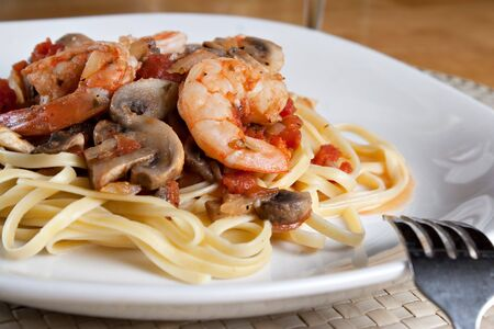 scampi: A delicious shrimp scampi pasta dish with mushrooms and diced tomatoes on a white plate.