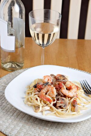 pinot grigio: A delicious shrimp scampi pasta dish with mushrooms and diced tomatoes along with a glass of pinot grigio white wine.