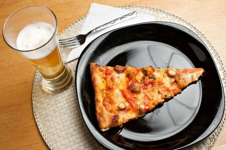 A single slice of buffalo chicken pizza and a glass of golden lager beer.  The perfect weekend take out dinner. photo
