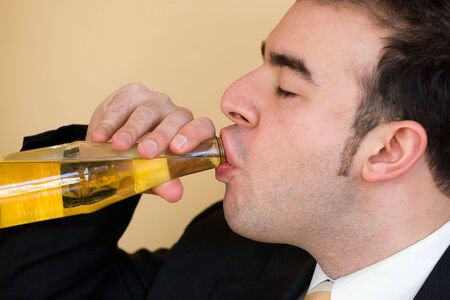 A young business man enjoying a nice cold bottle of beer after work. photo