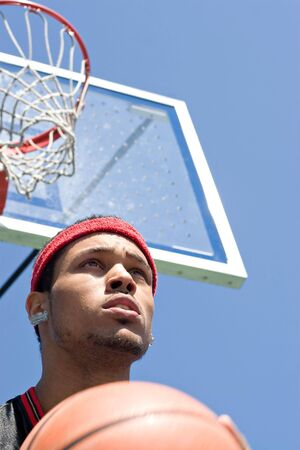 A basketball player holding the ball underneath the backboard and hoop. Stock Photo