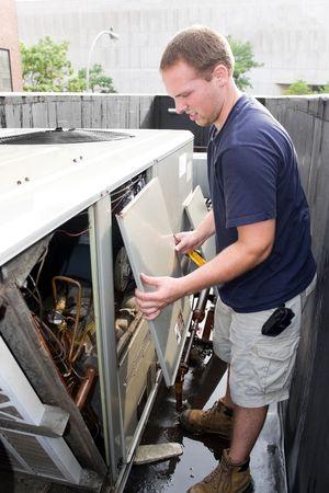 rooftop: Een airco verwarming ventilatie airconditioning technicus werkt op een grote commerciële eenheid. Stockfoto
