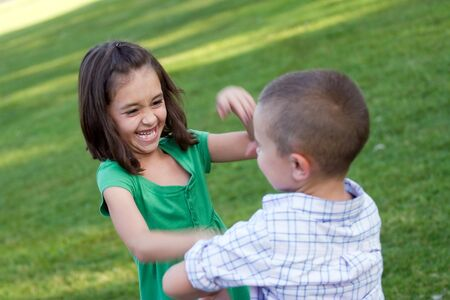 Two young sibling playfully hitting each other and rough housing.  Slight motion blur with sharp focus on the girls face. photo