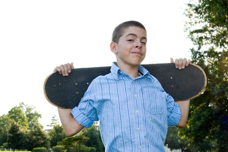 early teens: A boy in his early teens happily standing with his skateboard.