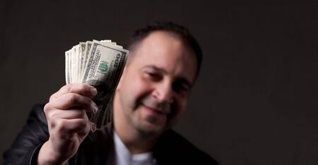 A happy middle aged man holding a handful of money with copyspace. photo