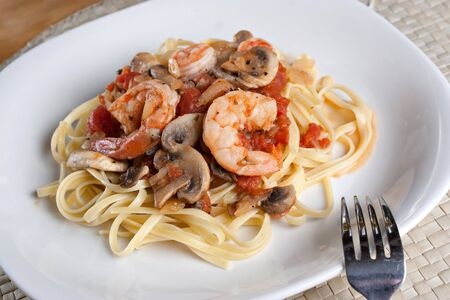 A delicious shrimp scampi pasta dish with mushrooms and diced tomatoes on a white plate. photo