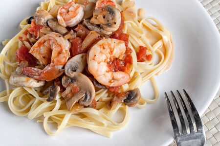 pinot grigio: A delicious shrimp scampi dinner with mushrooms and diced tomatoes on linguine pasta.
