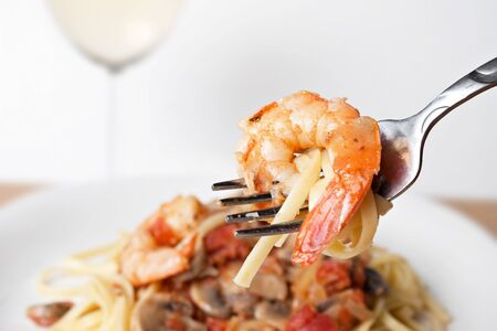 A delicious shrimp scampi pasta dish along with a glass of pinot grigio white wine.  Shallow depth of field with focus on the fork and shrimp. photo