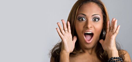 An amazed and shocked woman isolated over a silver background.  Lots of copy space for your text. photo