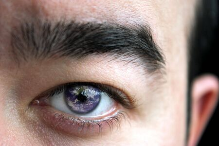 see  visionary: Closeup of a mans eye and eyebrow with the earth superimposed in his iris. Stock Photo