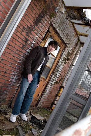 A young brunette man posing outside a worn and abandoned building. photo