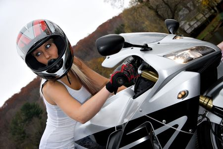 A pretty blonde girl seated on a modern motorcycle. photo