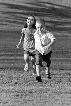 A little boy and girl laughing and running through the grassy field in black and white. photo