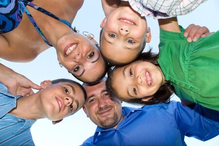 A happy family posing in a group huddle formation.  Shallow depth of field. Standard-Bild