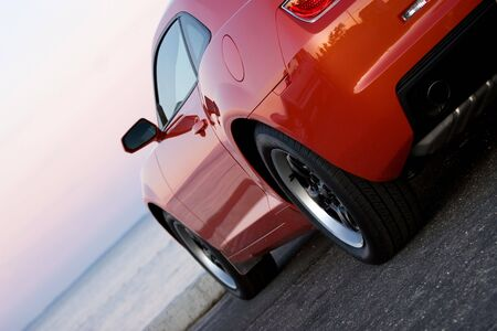custom car: A modern sports car parked at the beach around sunset.