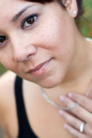 heirlooms: A young woman wearing a necklace and a diamond ring.  Shallow depth of field with sharp focus on her face.