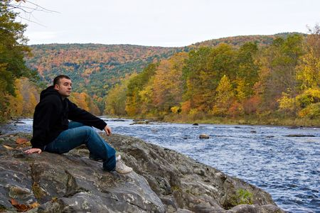 A young man enjoying the peaceful and beautiful sites and sounds of a Vermont river during peak Autumn foliage.  photo