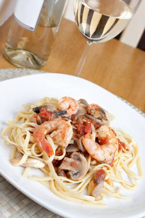 A delicious shrimp scampi over linguine dish along with a glass of pinot grigio white wine.  photo