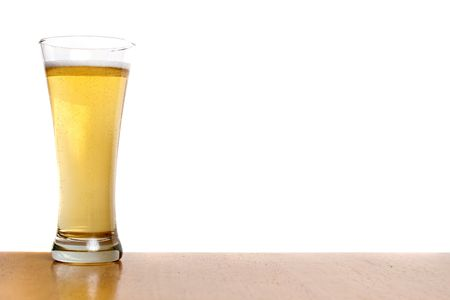 pilsner: A pilsner glass filled to the top with fresh beer isolated over white. Stock Photo