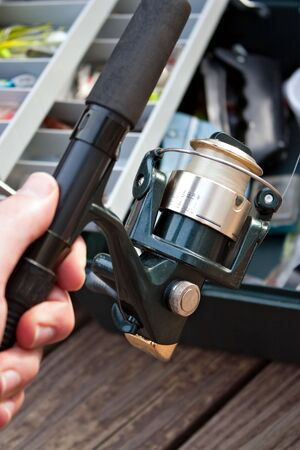 A hand holding a fishermans rod reel and tackle box ready for the start of fishing season. photo