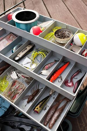 tackle: A fully stock fishermans tackle box fully stocked with lures and gear for fishing.