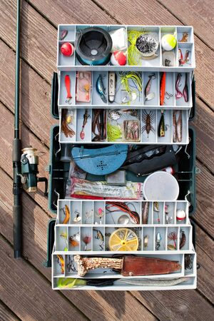fishing tackle: A fully stock fishermans tackle box rod and reel ready for a long day of fishing.
