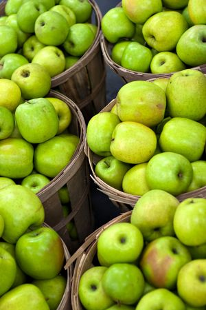 apples basket: Bushels full of fresh granny smith or golden delicious green apples. Shallow depth of field. Stock Photo