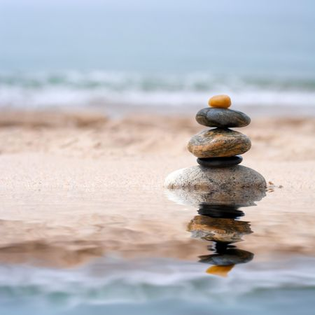 A pile of round smooth zen like stones stacked in the sand at the beach.