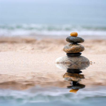 balanza: Un mont�n de ronda zen suave como piedras apiladas en la arena en la playa.  Foto de archivo